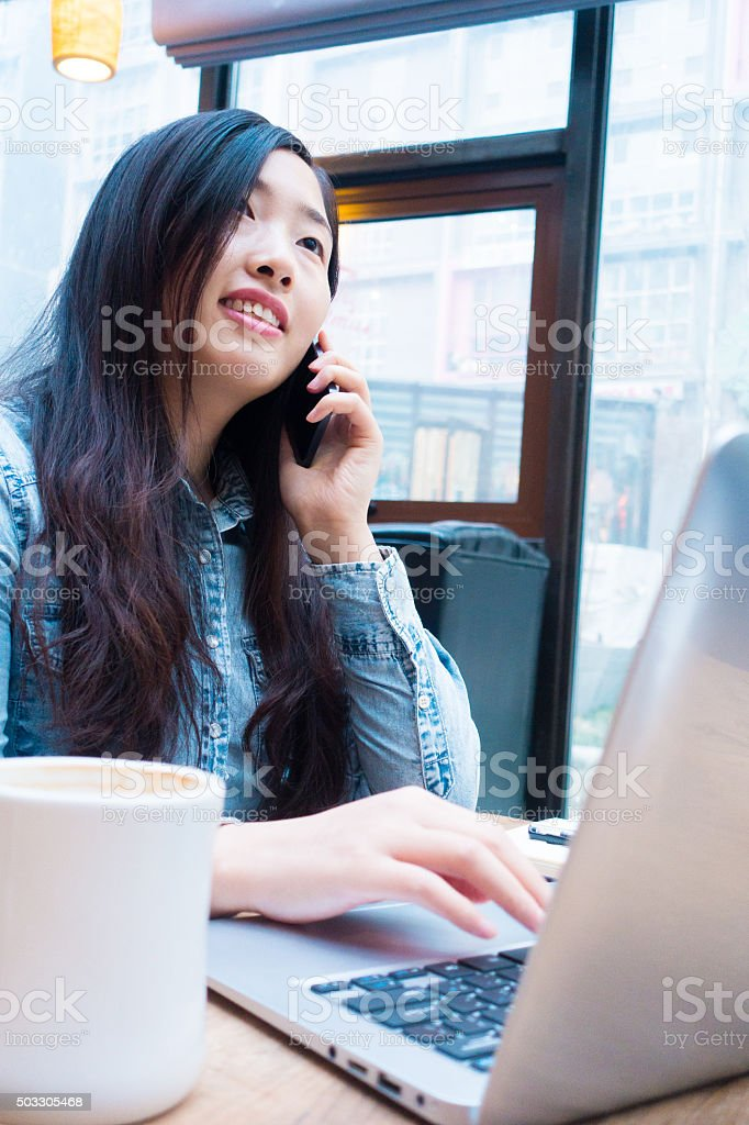 young businesswoman woking with mobile phone and laptop stock photo