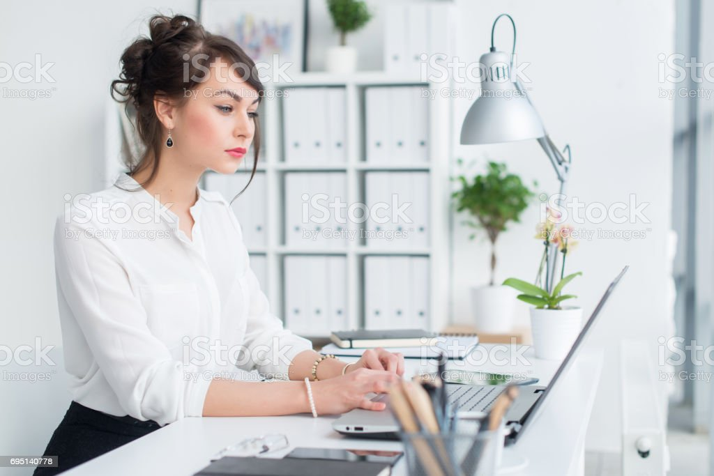 Young businesswoman working in office, typing, using computer. Concentrated woman searching information online stock photo