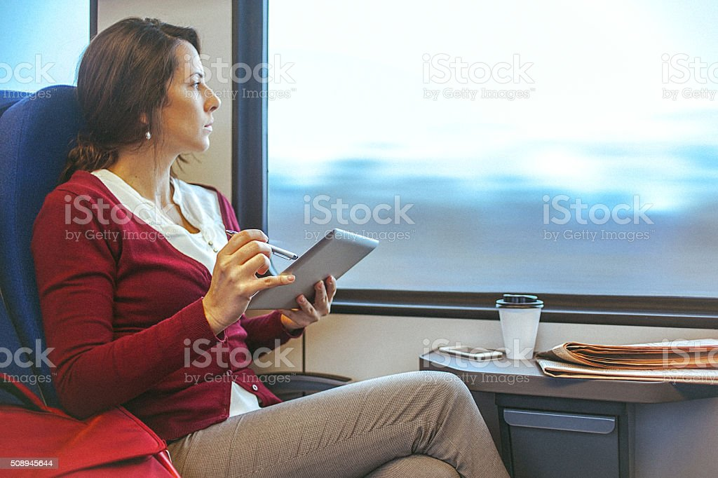 Young businesswoman working on tablet while commuting to work stock photo