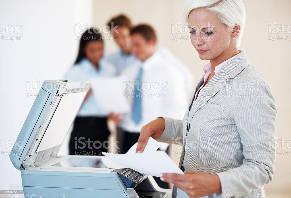 Young businesswoman working on xerox machine stock photo