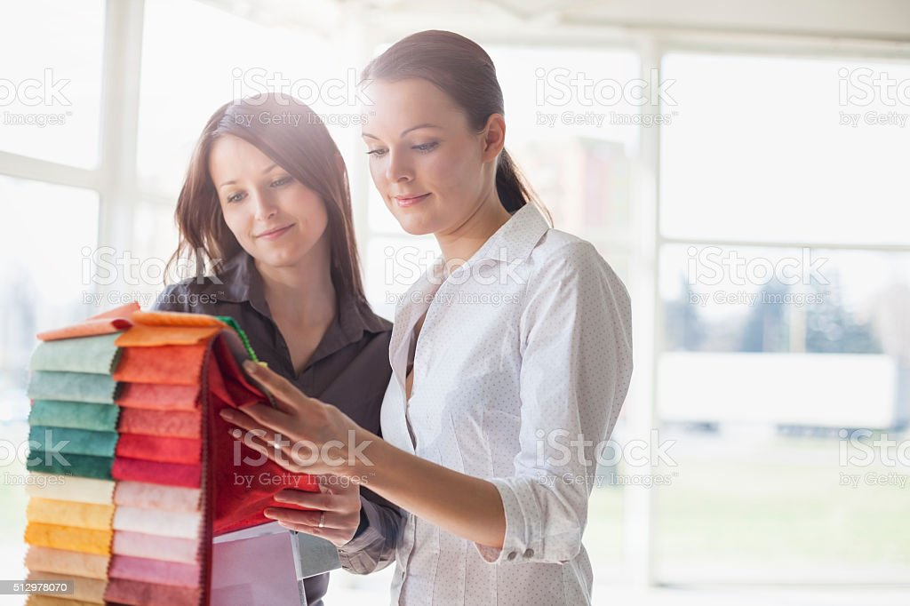 Young businesswomen choosing fabric swatches in office stock photo