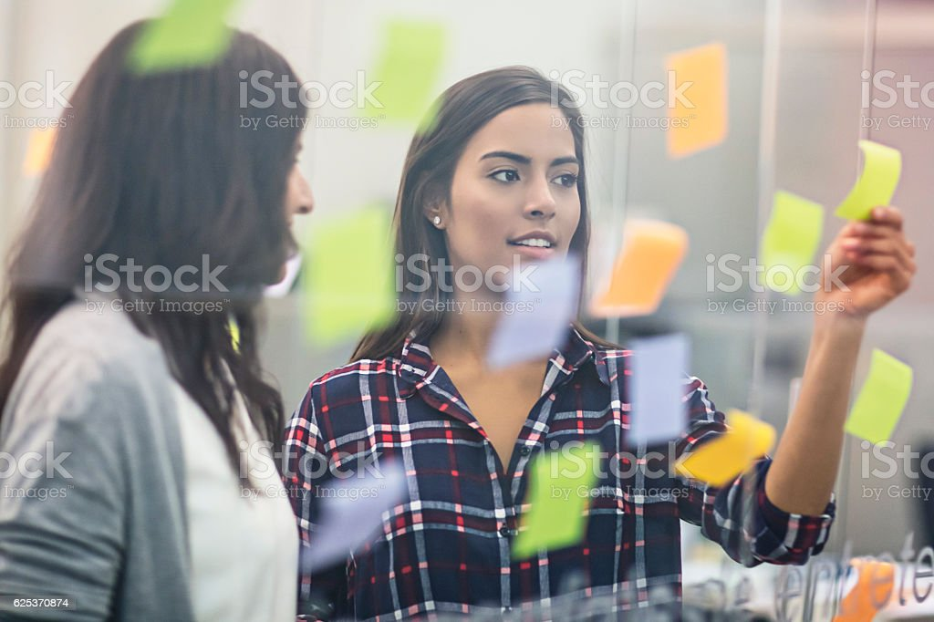 Young businesswomen discussing over sticky notes on glass stock photo