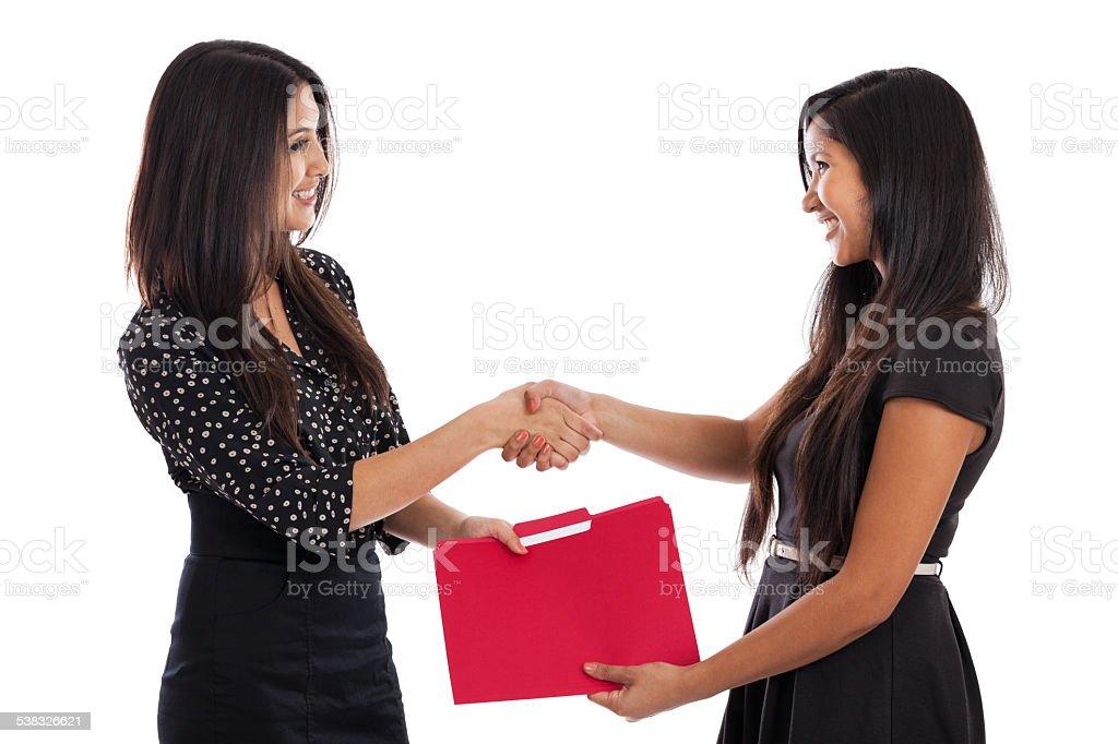 Young businesswomen shaking hands stock photo