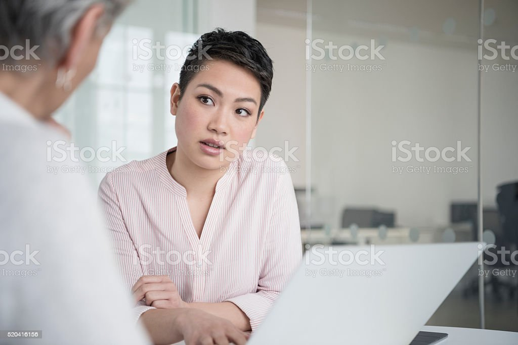 Young businesswomen with short black hair listening in meeting stock photo