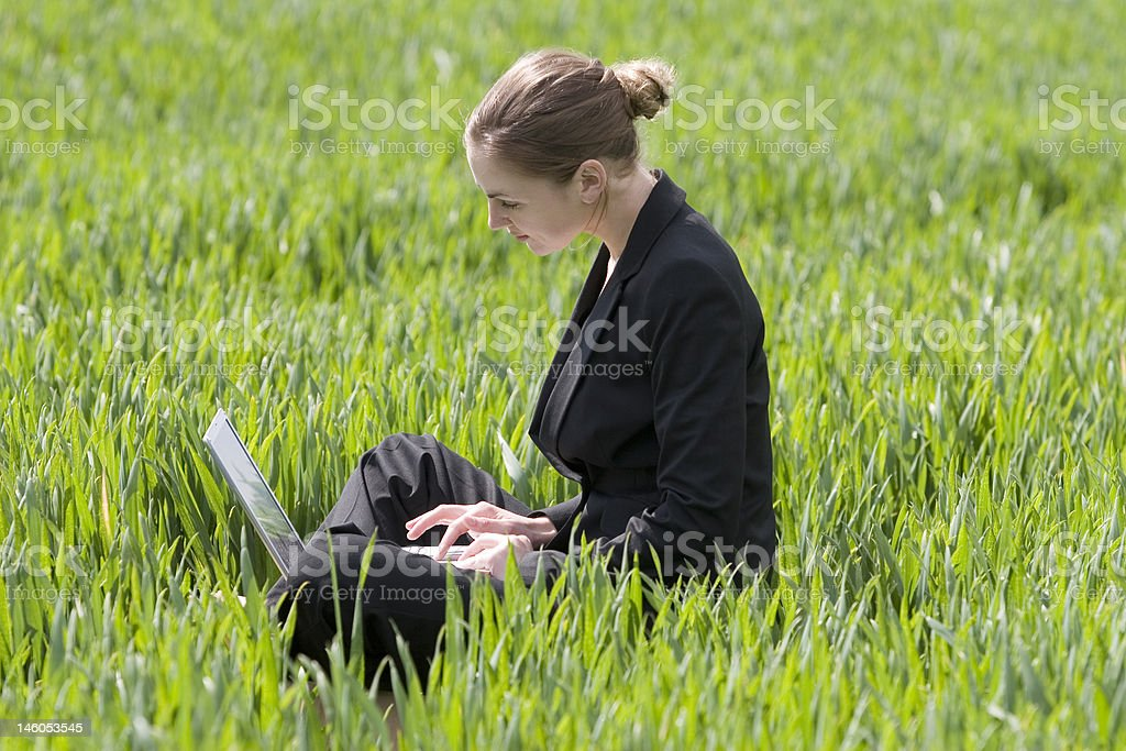 Young businesswomen works on laptop in field royalty-free stock photo