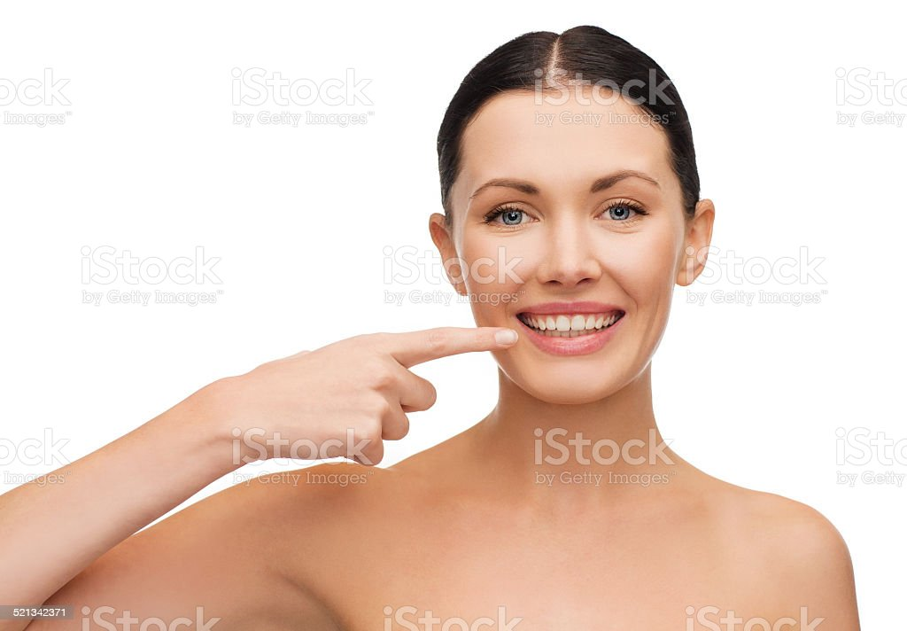 young calm woman pointing to her mouth stock photo