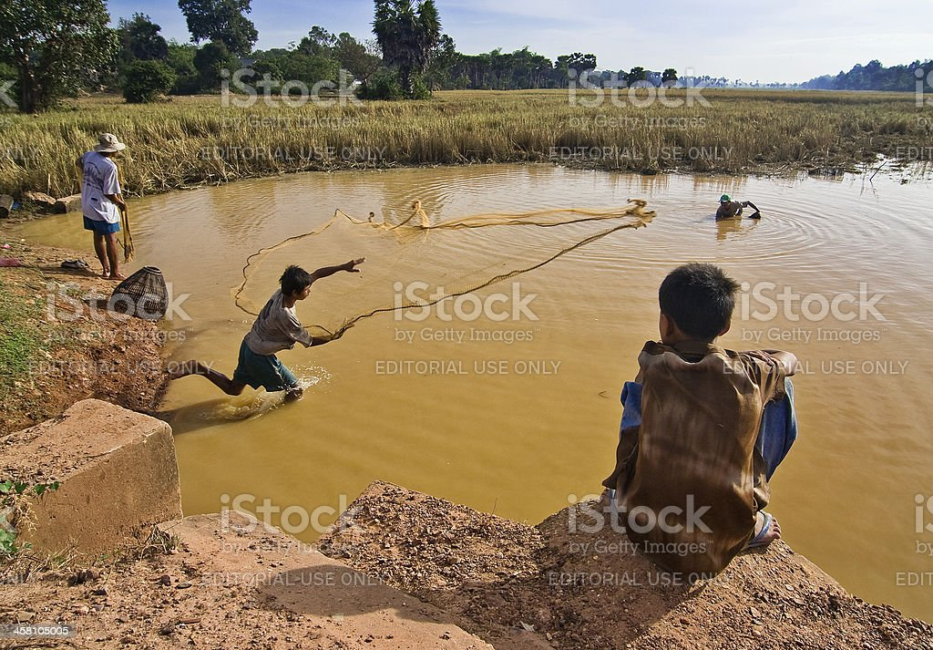 Young Cambodian male casting a fishing net royalty-free stock photo