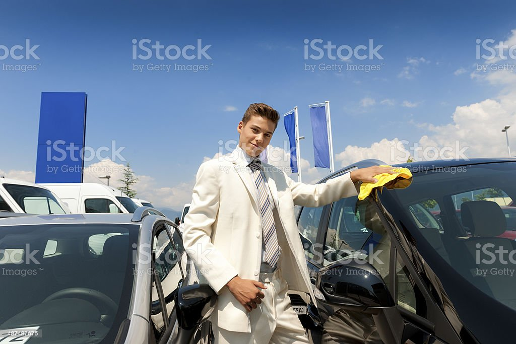 Young car salesman at dealership stock photo