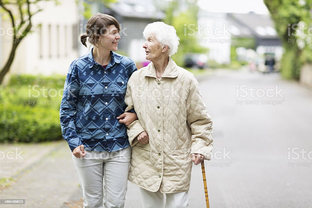 young caregiver helping senior woman walking in the street stock photo