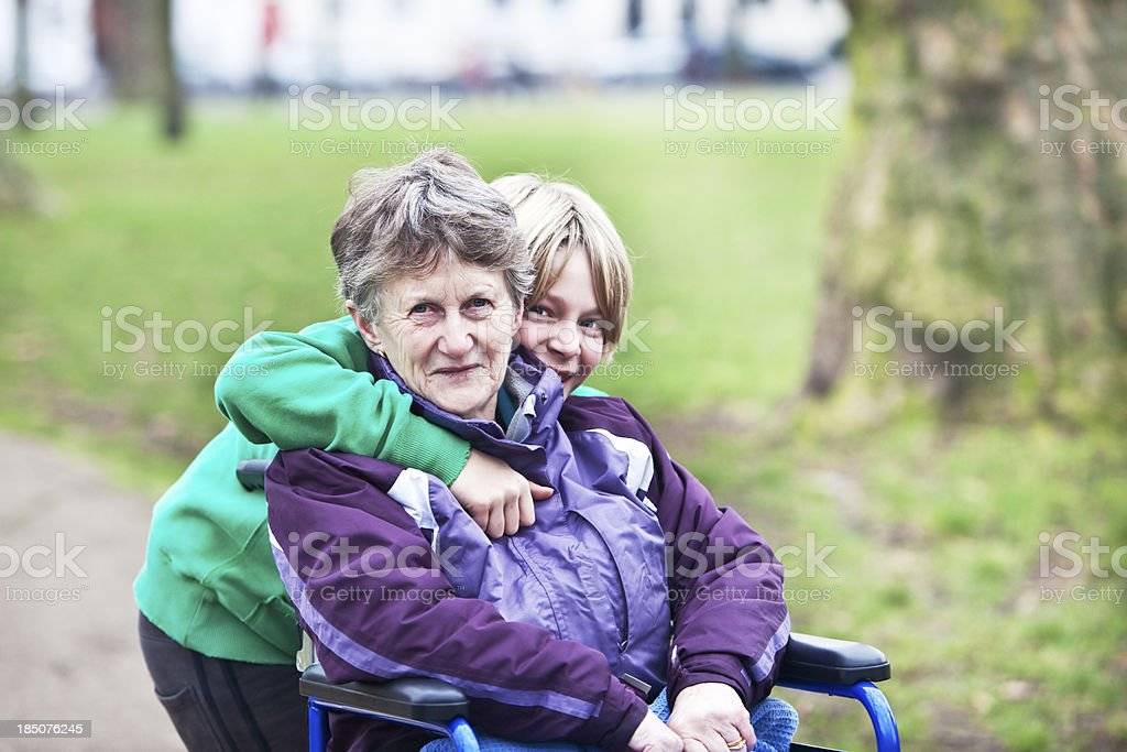 young carer out with his grandmother in a wheelchair royalty-free stock photo
