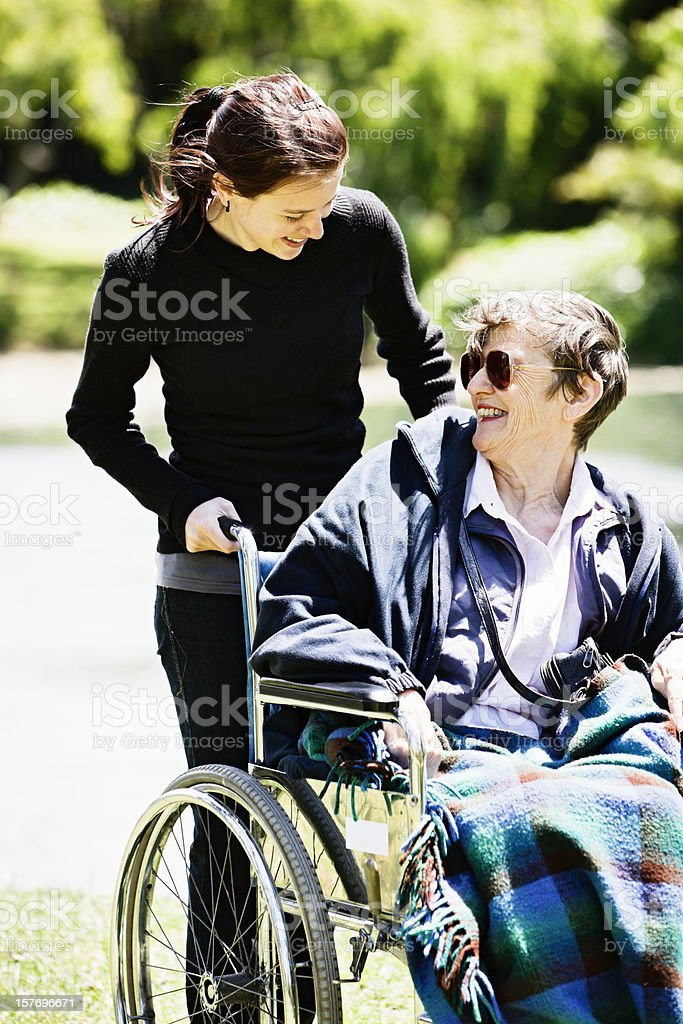 Young carer smiles at happy old woman in wheelchair royalty-free stock photo