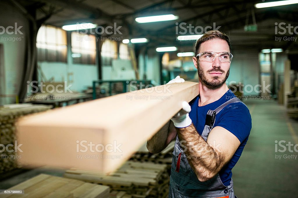 Young carpenter carrying wood plank stock photo