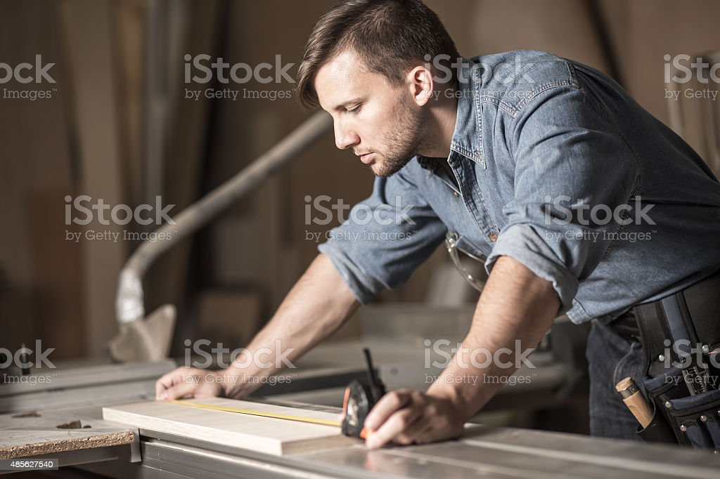 Young carpenter using measuring tape stock photo