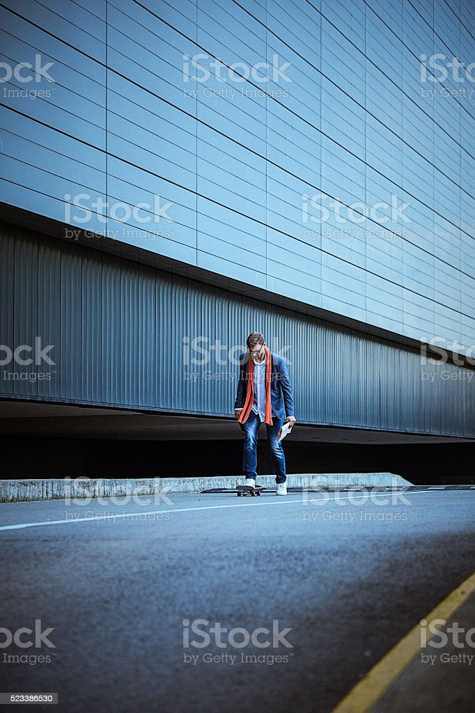 Young casual businessman comuting to work skateboarding. stock photo