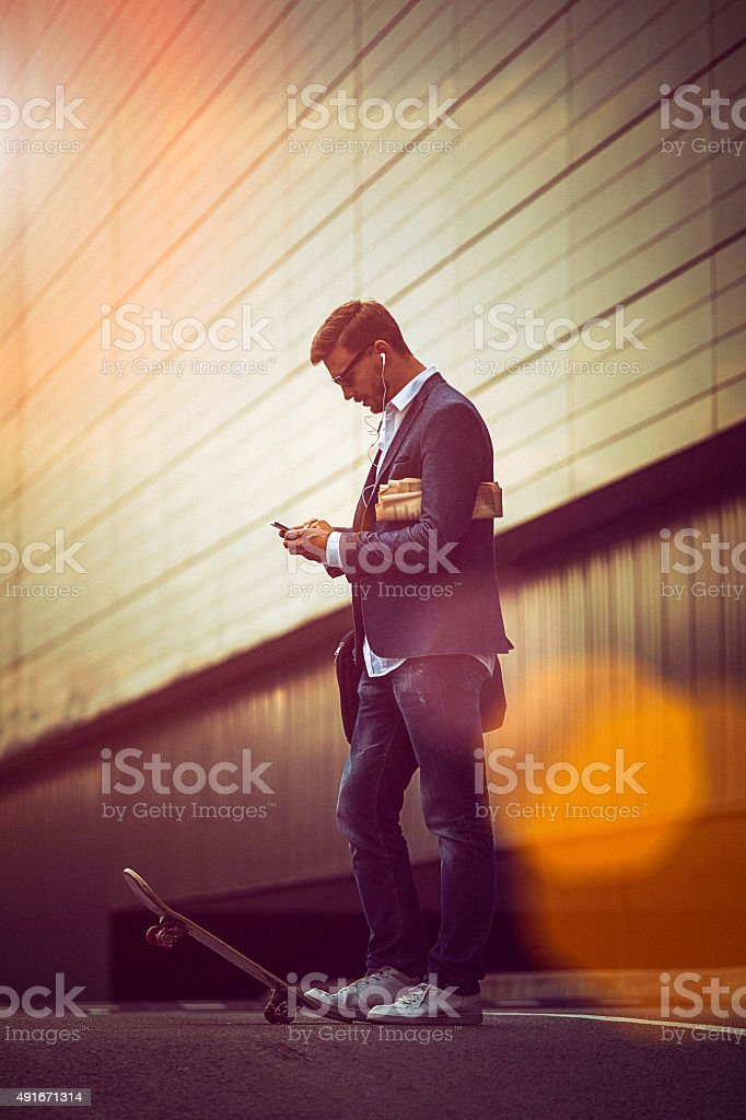 Young casual businessman using smartphone in the urban environme stock photo