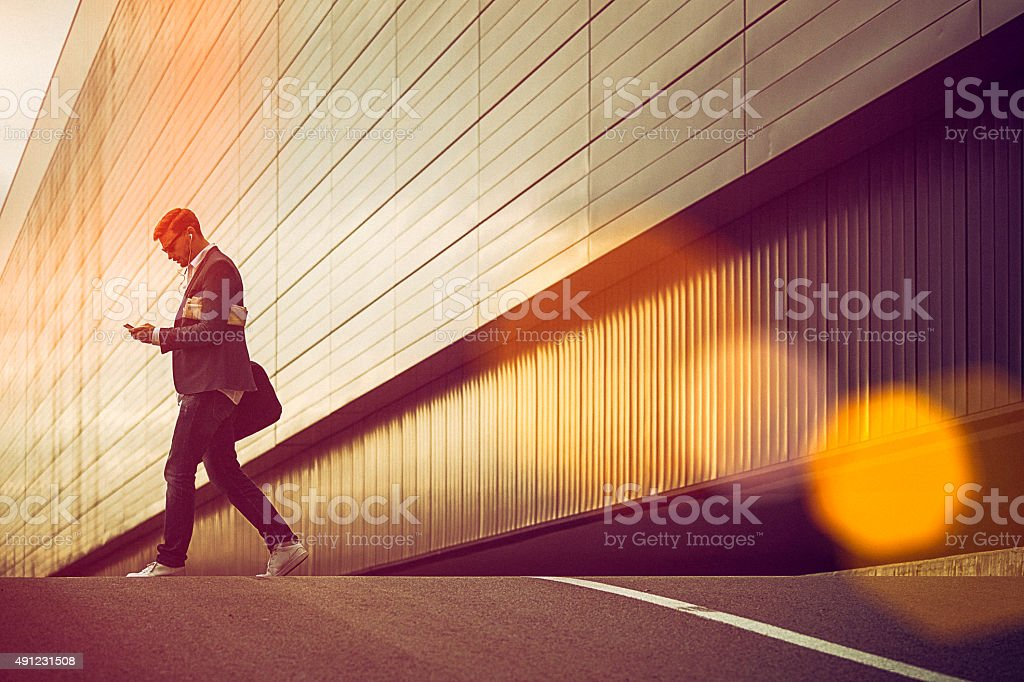 Young casual businessman using smartphone in the urban environment stock photo