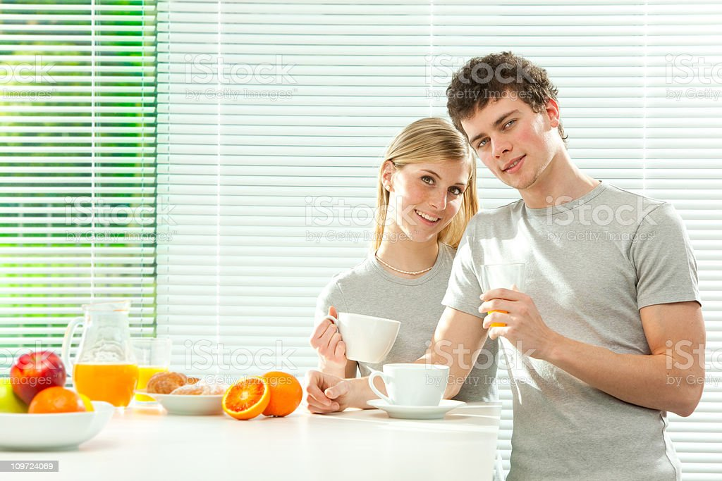 Young casual couple has breakfast with fruit juice and coffee royalty-free stock photo