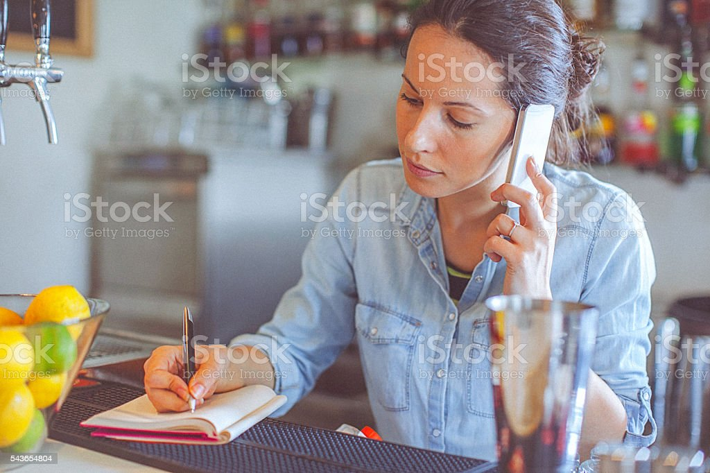 Young, casual female bar owner ordering merchandise stock photo
