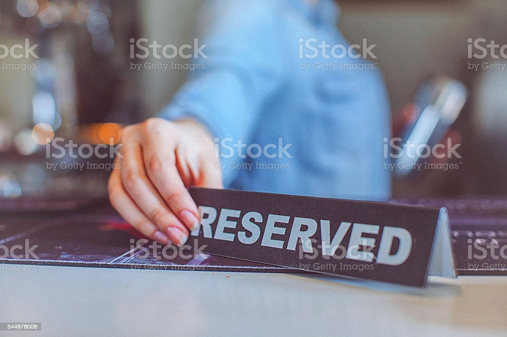 Young casual female bartender placing reserved sign on bar counter stock photo