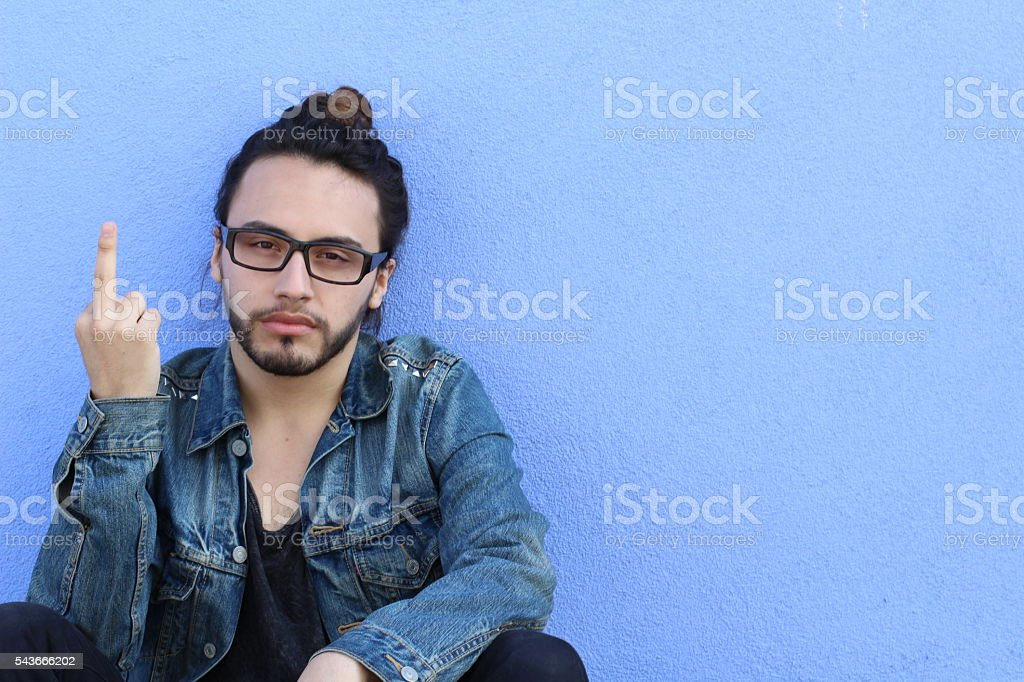 Young casual hipster man showing you the middle finger stock photo