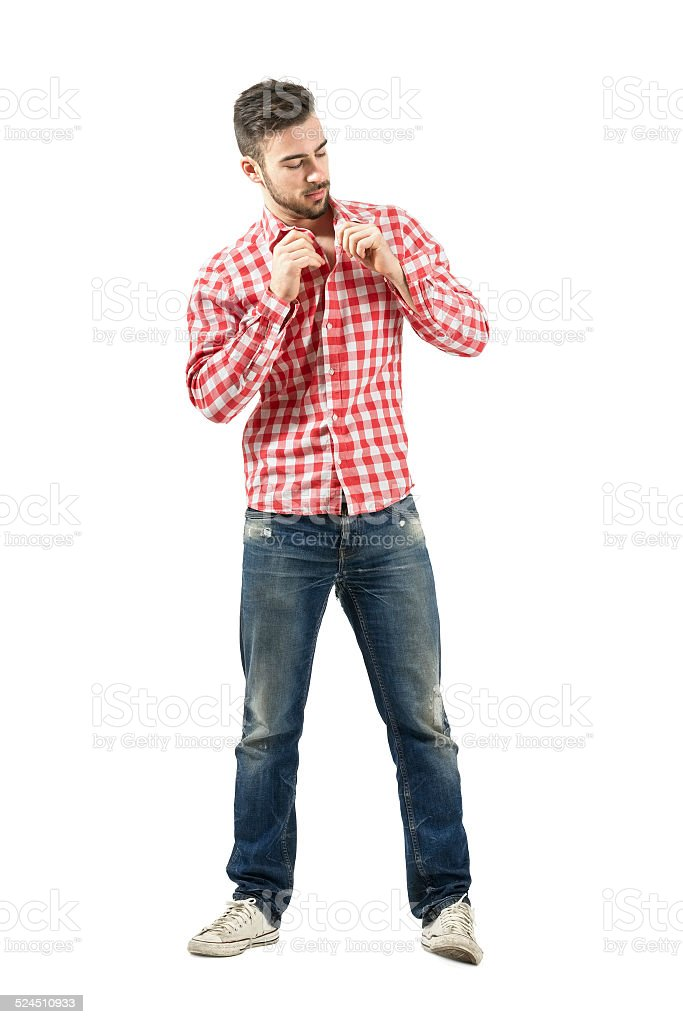 Young casual man buttoning plaid shirt stock photo