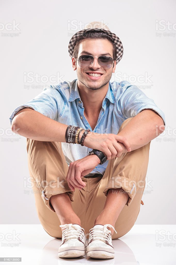 Young casual man sitting on studio background stock photo