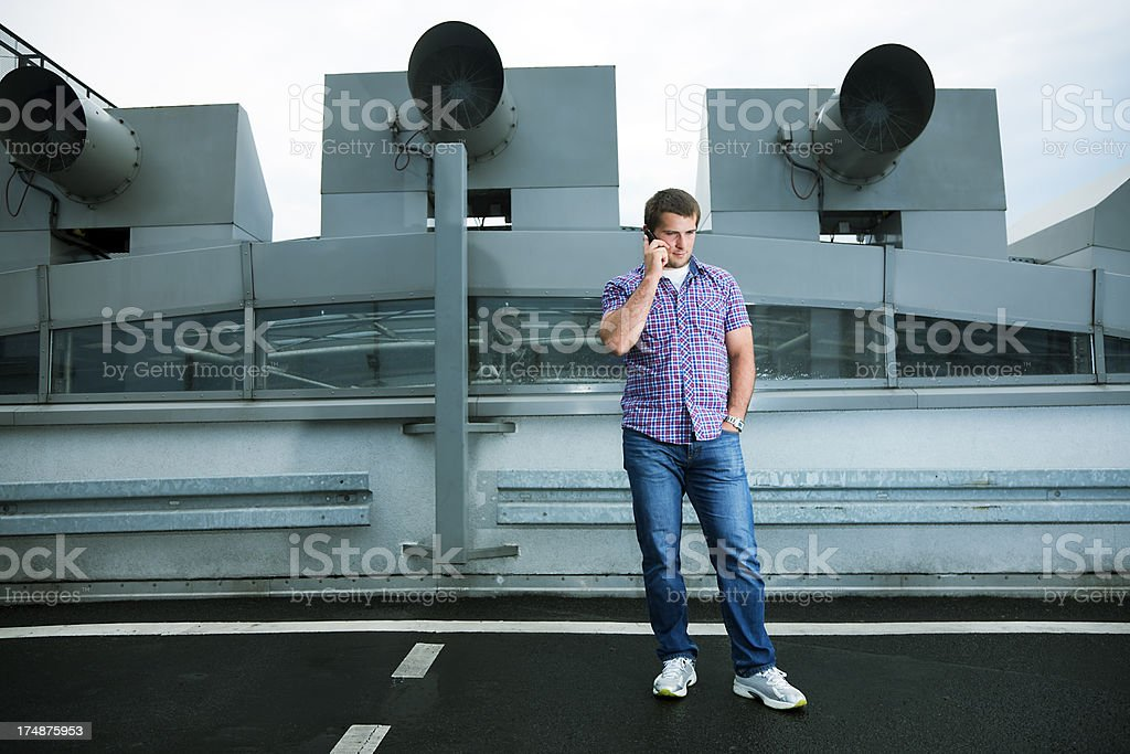 Young Casual Man Using Mobile Phone in Parking Lot Roof royalty-free stock photo