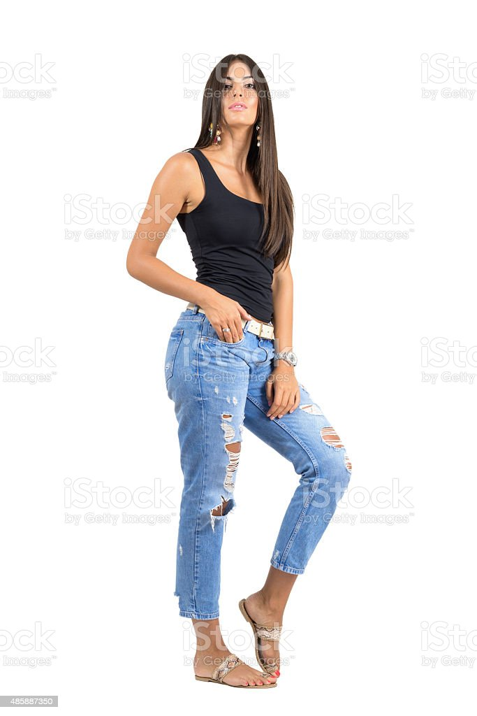 Young casual woman in torn jeans posing at camera. stock photo