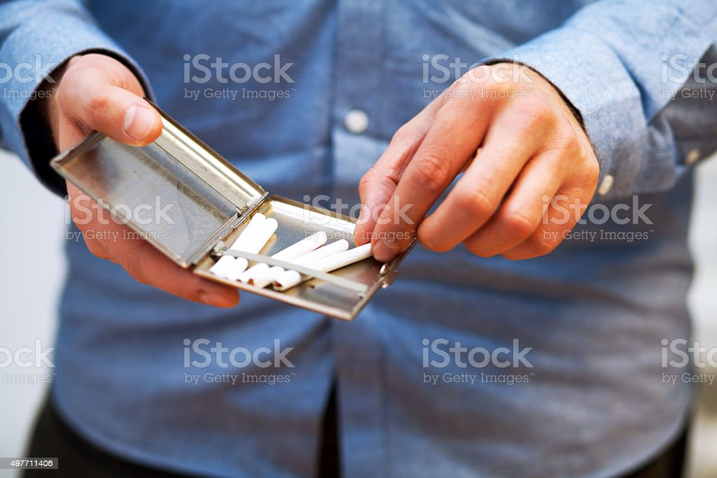 Young caucasian adult is taking self rolled cigarette stock photo