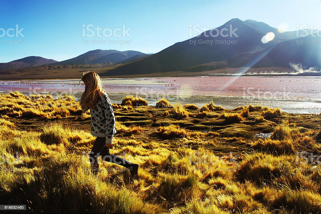 young caucasian blond woman walking at lagoon Colorada, Bolivia stock photo