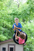 Young Caucasian Boy and Girl on a Tire Swing