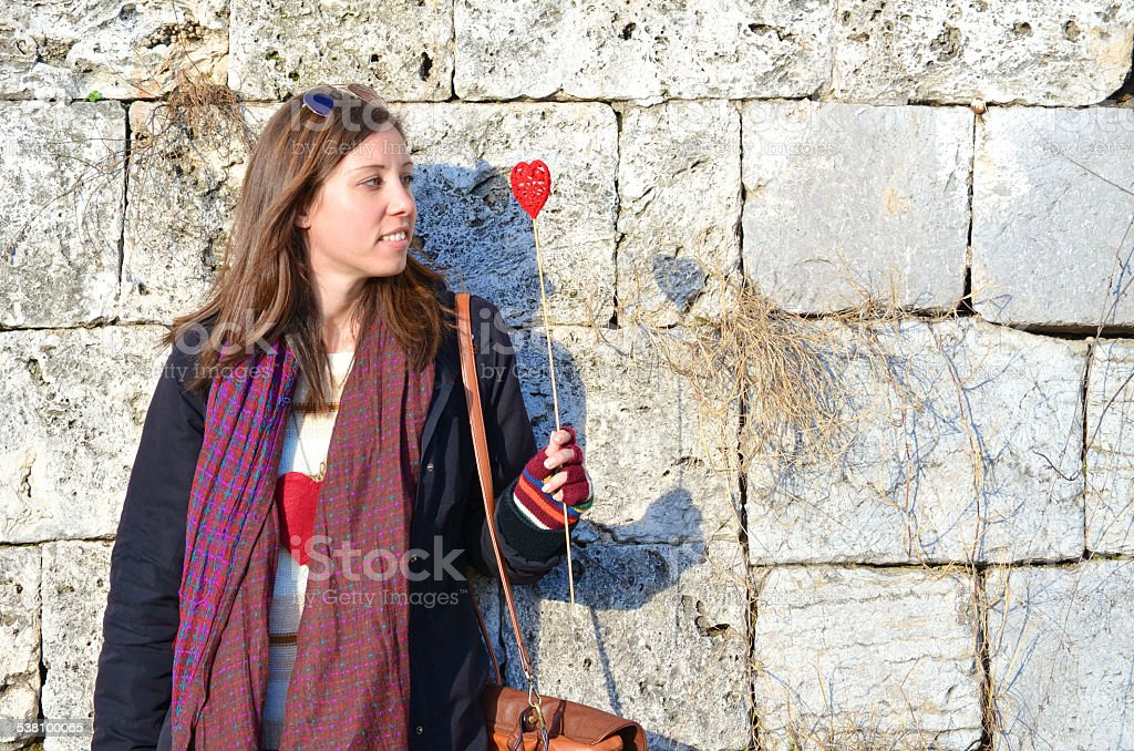 Young Caucasian brunette looking at a red heart royalty-free stock photo