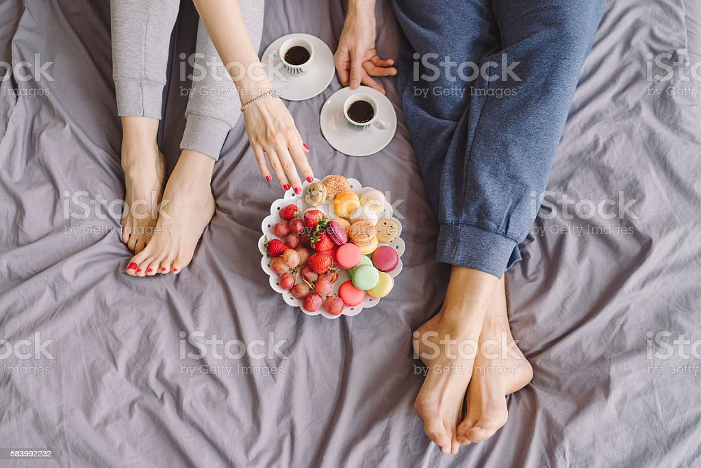 Young caucasian couple having romantic breakfast in bed stock photo
