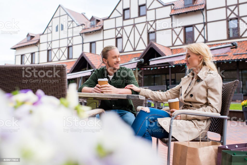 young caucasian couple talking while drinking disposable coffee at cafe on the street stock photo