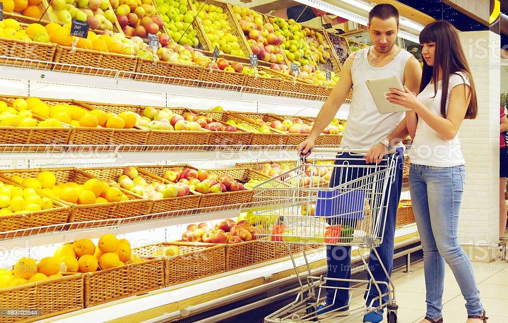 Young caucasian couple walking in a supermarket with  market trolley foto de stock libre de derechos