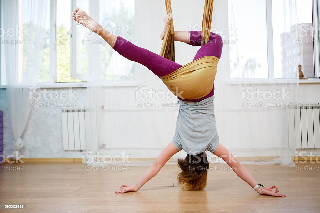 Young caucasian girl posing aerial yoga with hammock in class stock photo