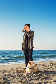 young caucasian male drinking coffee on beach, walking with dog
