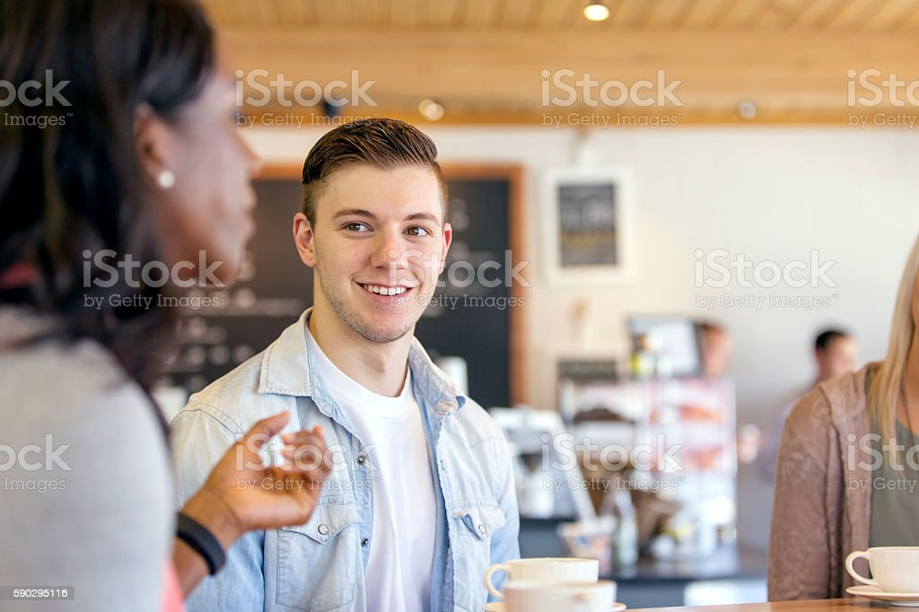 Young caucasian male talking with friends stock photo