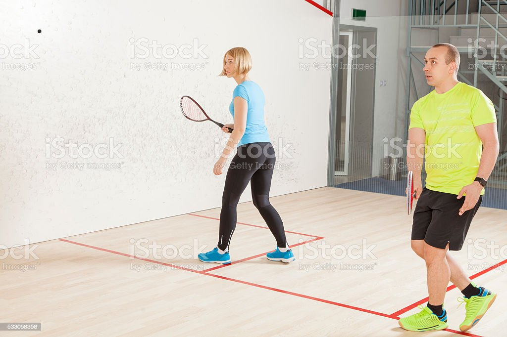 Young caucasian man and woman playing squash. stock photo