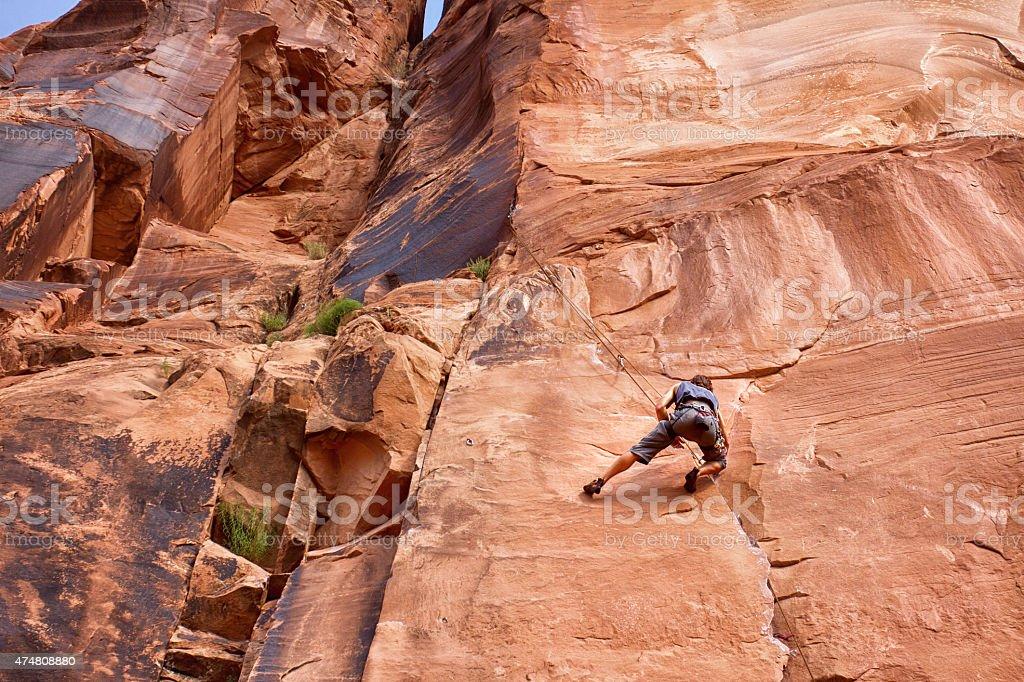 Young Caucasian Man Climbing a Rock Wall Near Moab stock photo