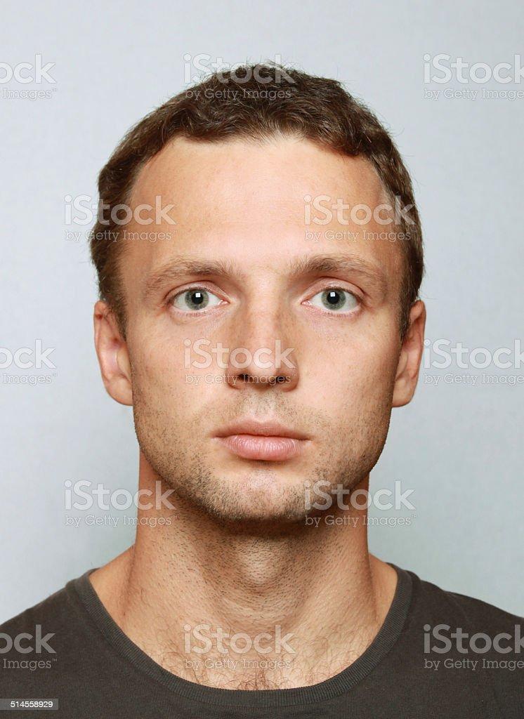 Young Caucasian man closeup portrait. Headshot on gray stock photo