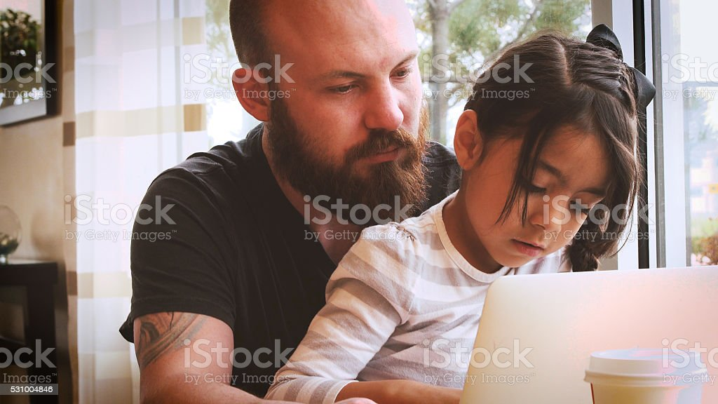 Young Caucasian Man Helping Little Hispanic Girl with Laptop stock photo