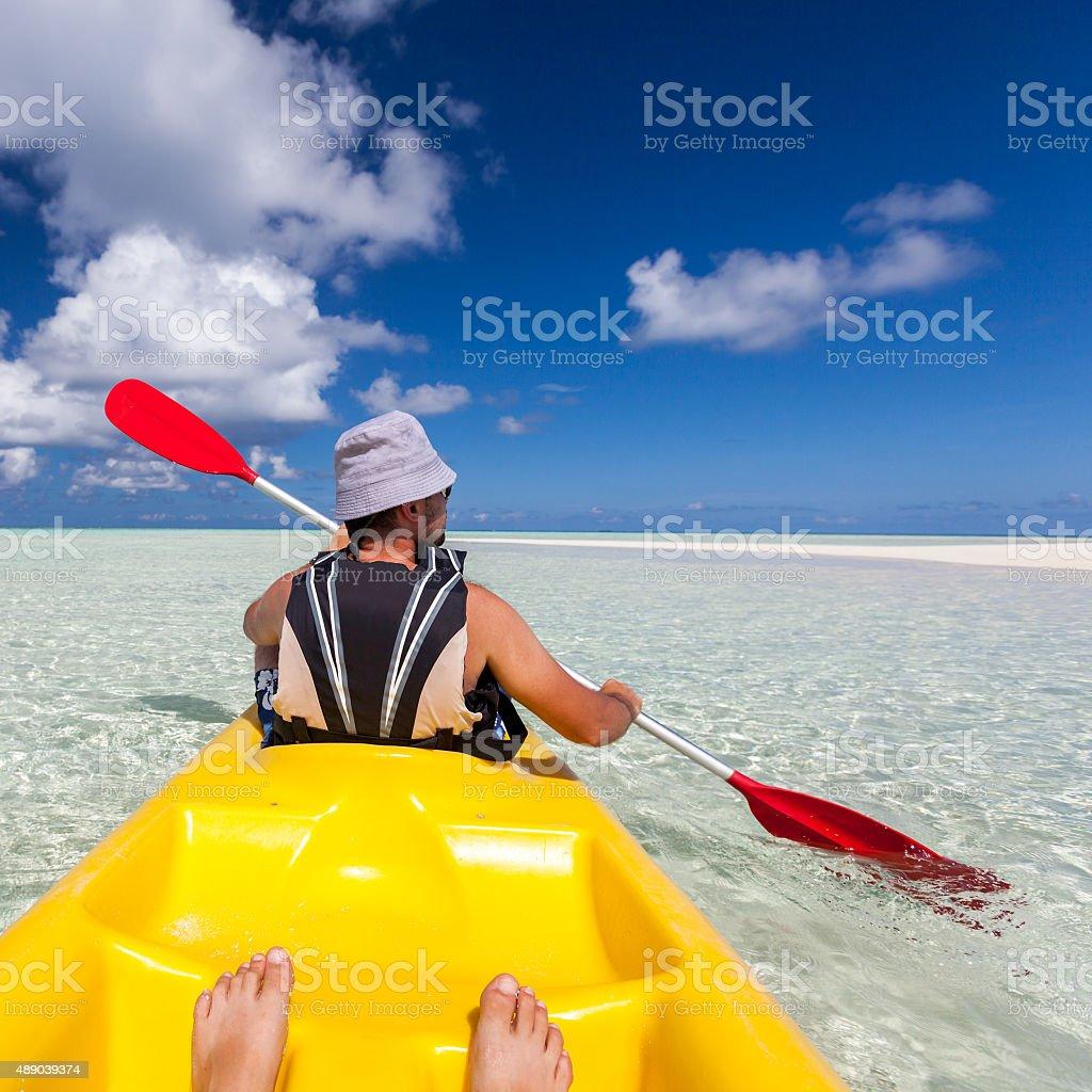 Young caucasian man kayaking in sea at Maldives stock photo