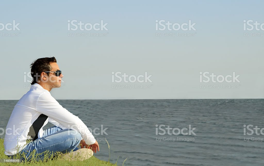 young caucasian man sitting alone and looking to the sea royalty-free stock photo