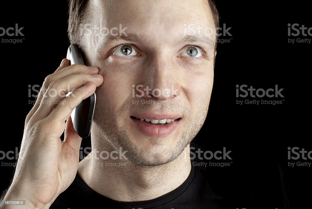 Young Caucasian man talks on mobile phone above black background royalty-free stock photo