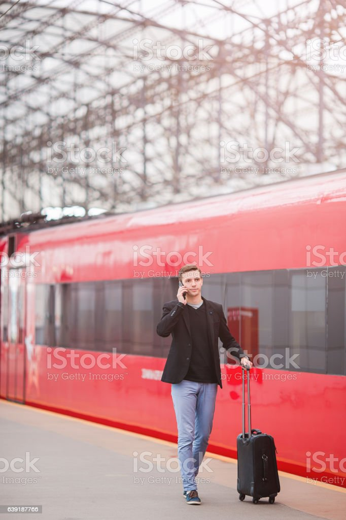 Young caucasian man with luggage at station traveling by train stock photo