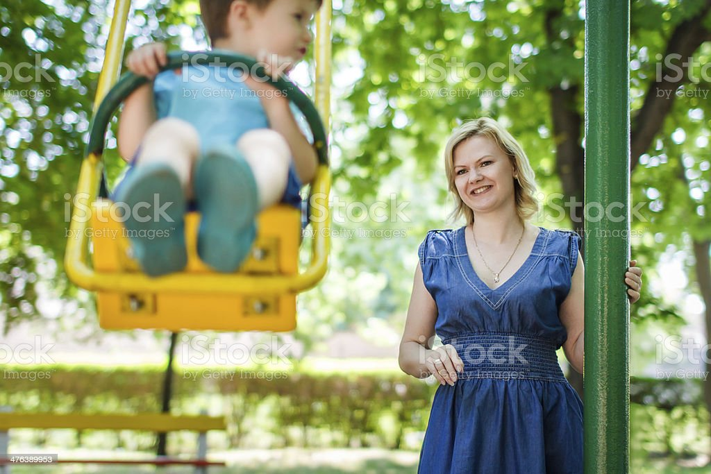 Young caucasian mother with swinging son at playground royalty-free stock photo