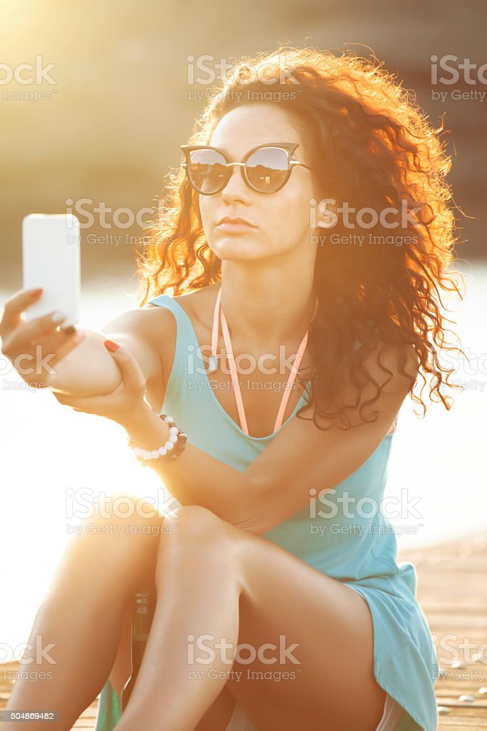 Young caucasian white woman sitting on the quay stock photo