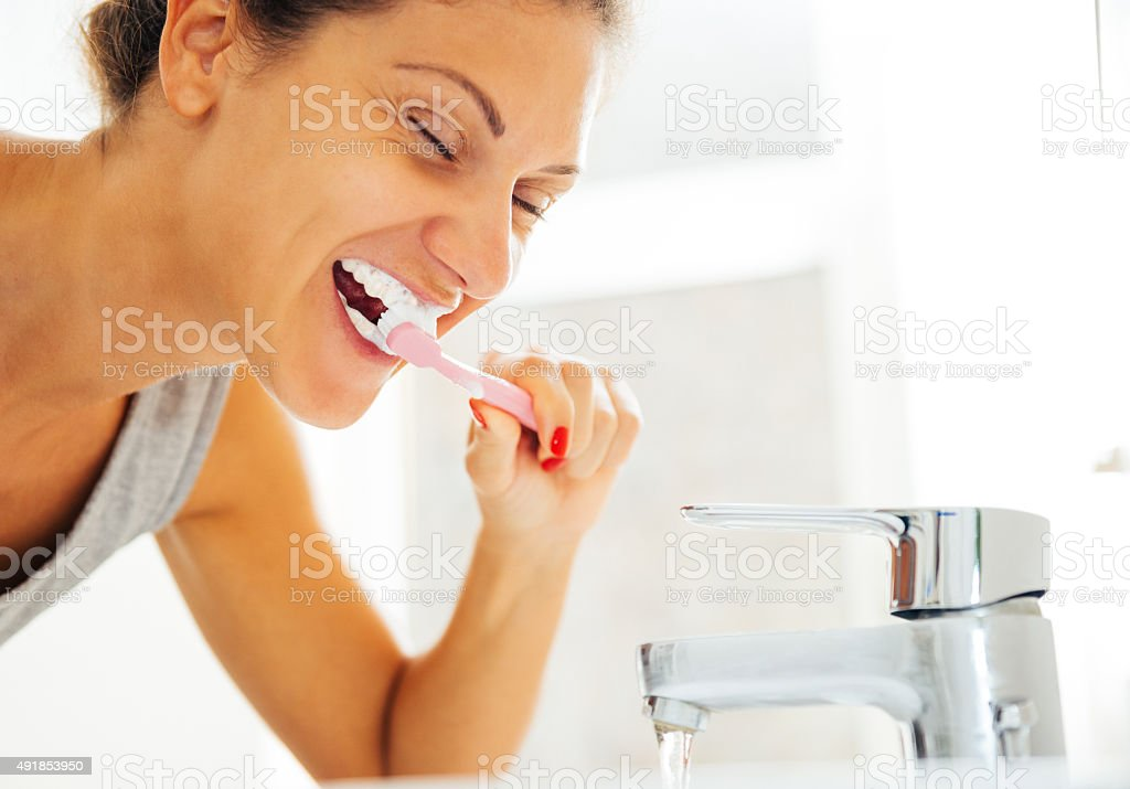 Young caucasian woman brushing her teeth in bathroom in morning stock photo