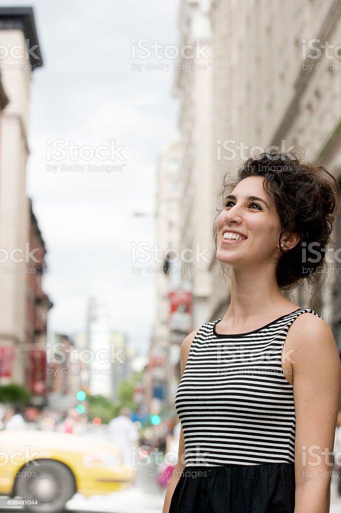 Young Caucasian woman looking upward in downtown city stock photo